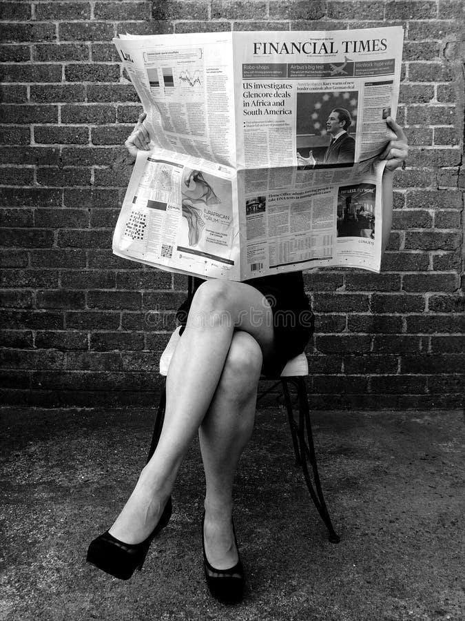 Den unga affärskvinnan läser Financial Times royaltyfria bilder