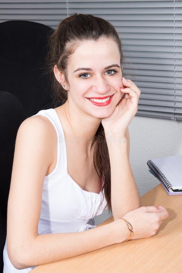 den unga affärskvinnan sitter i regeringsställning skrivbordhanden under hakan royaltyfri fotografi