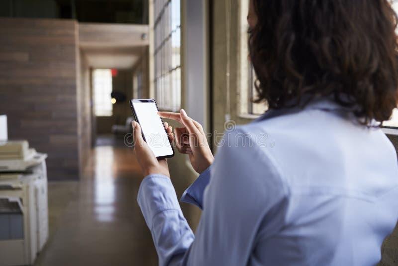 Den unga affärskvinnan som i regeringsställning använder smartphonen, beskådar tillbaka fotografering för bildbyråer