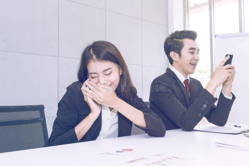Den unga affärskvinnan talar i hemlighet på telefonen på arbete arkivbild