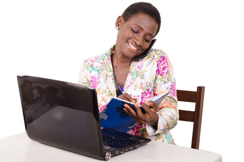 Den unga affärskvinnan tar anmärkningar, genom att meddela arkivbild