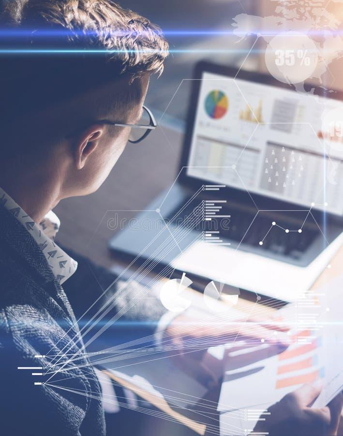 Den unga affärsmannen analyserar materielrapporten på anteckningsbokskärmen Begrepp av den digitala skärmen, symbol för faktisk a arkivbilder