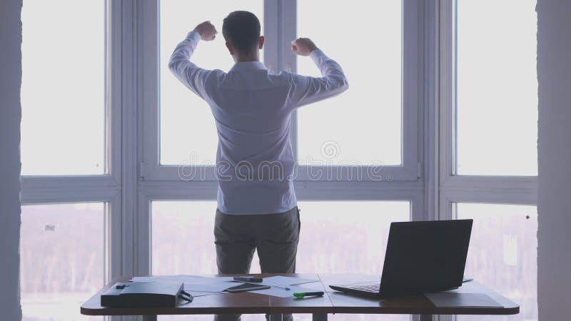 Den unga affärsmannen beundrar sikt från fönstret grep hårt om hans nävar i ett kontor arkivbilder