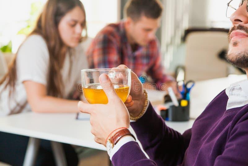 Den unga affärsmannen dricker te, medan hans kollegor på bakgrund arbetar hårt royaltyfri bild