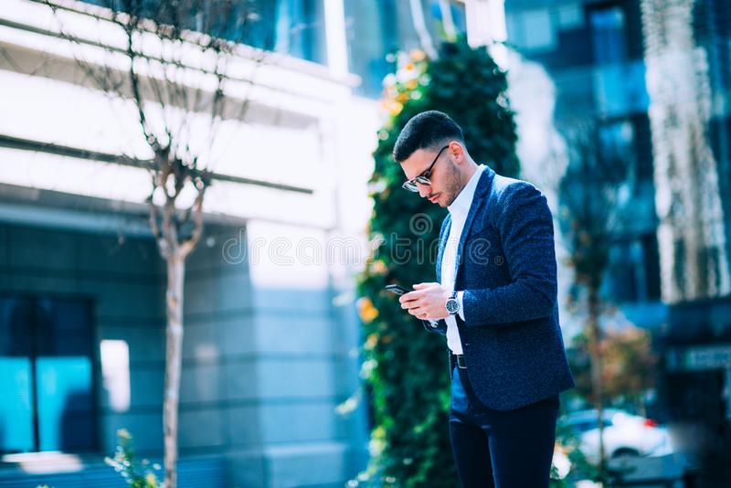Den unga affärsmannen går omkring och talar på hans telefon på den finansiella mitten för staden fotografering för bildbyråer