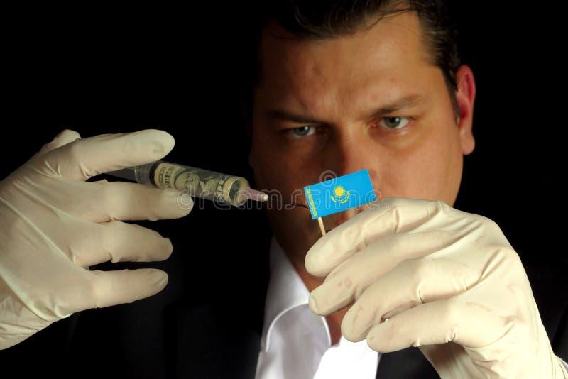 Den unga affärsmannen ger en finansiell injektion till den Kazakhstani flaggan royaltyfri bild