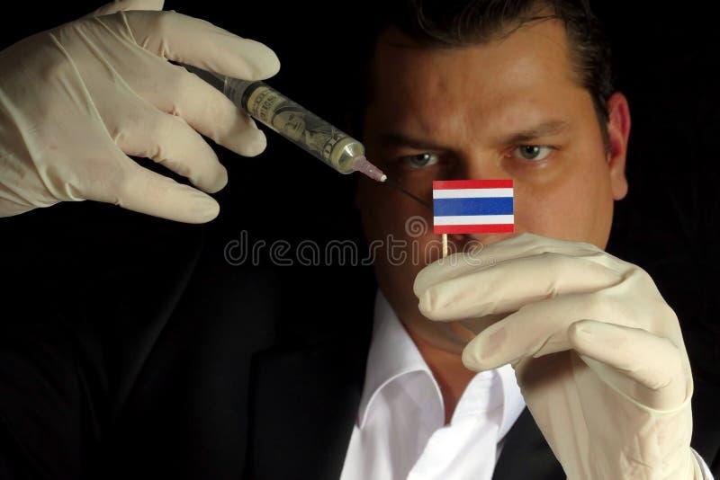 Den unga affärsmannen ger en finansiell injektion till den thailändska flaggaisolaen royaltyfria bilder