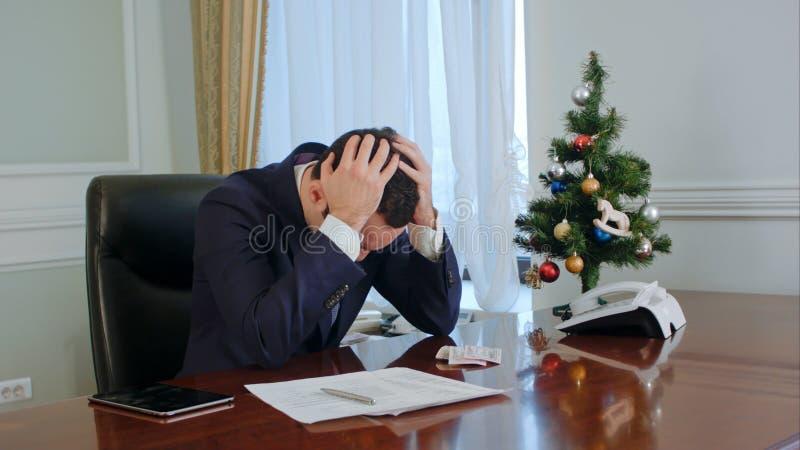 Den unga affärsmannen i en dräkt gnider hans näsa, har att se ner ingen idé och som tröttar Vi förstår från hans framsida att han royaltyfria bilder