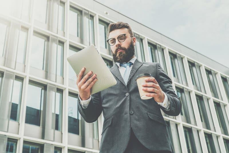 Den unga affärsmannen i glasögon, dräkt och band står utomhus-, använder minnestavladatoren och dricker kaffe arkivbild