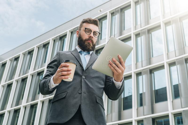 Den unga affärsmannen i glasögon, dräkt och band står utomhus-, använder minnestavladatoren och dricker kaffe arkivfoton