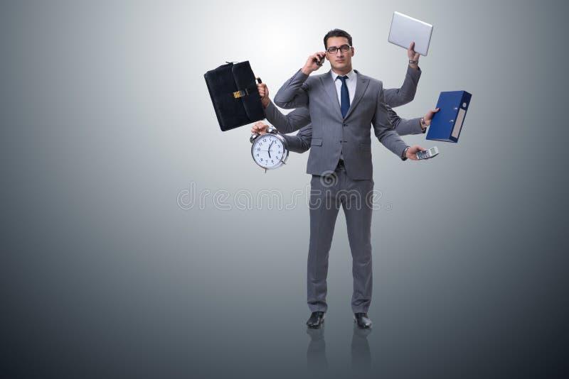 Den unga affärsmannen i multitaskingbegrepp arkivbilder