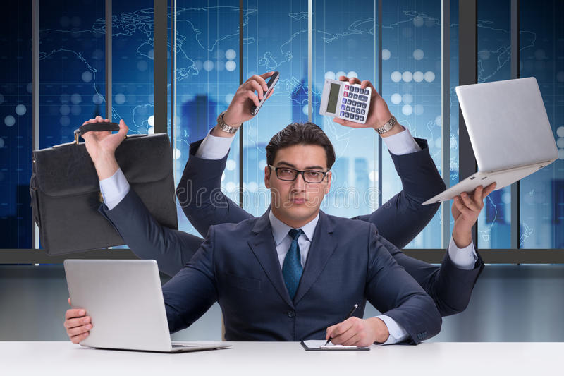 Den unga affärsmannen i multitaskingbegrepp arkivfoton