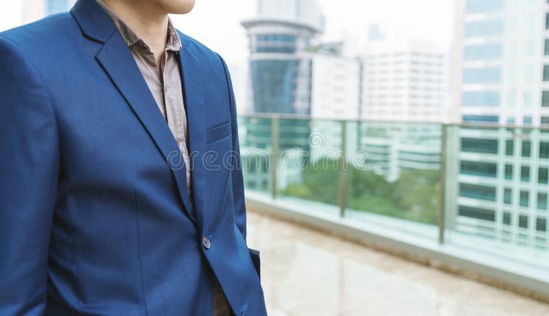 Den unga affärsmannen i smarta tillfälliga blått passar på skyskrapabyggnad fotografering för bildbyråer