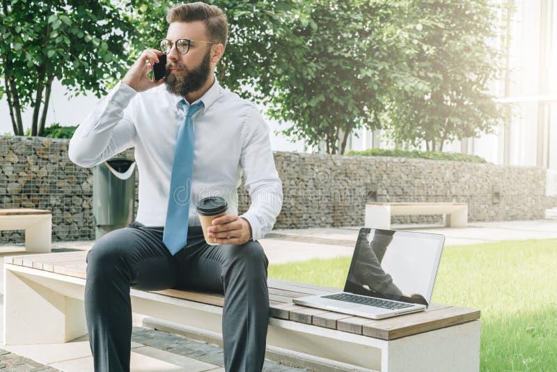 Den unga affärsmannen i den vita skjortan och bandet sitter utanför på bänk, dricker kaffe och talar på hans mobiltelefon royaltyfri fotografi