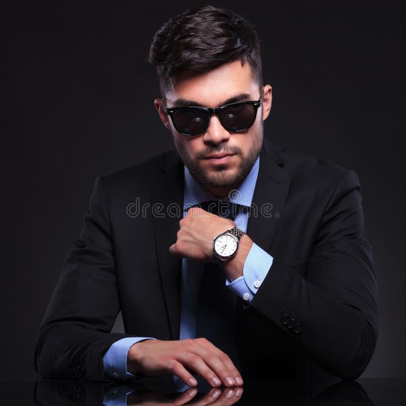 Den unga affärsmannen justerar hans band royaltyfri fotografi