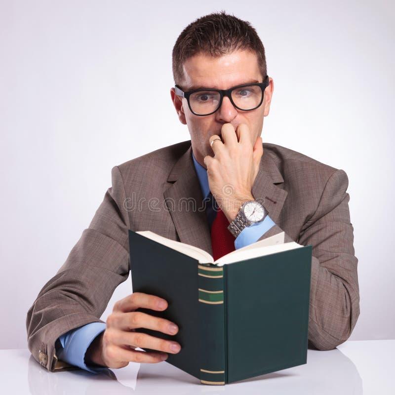Den unga affärsmannen läser en läskig bok royaltyfria bilder