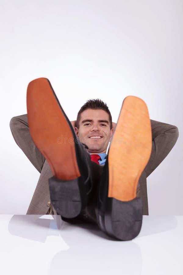 Den unga affärsmannen ler med händer bak huvudet och fot på des arkivbild