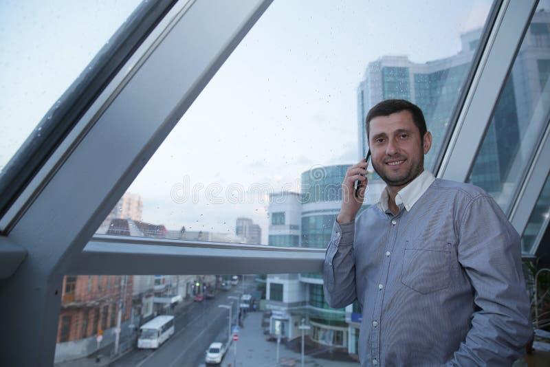 Den unga affärsmannen med ett leende på hans framsida talar på hans mobiltelefon mot bakgrunden av ett panorama- fönster på ett h arkivfoton
