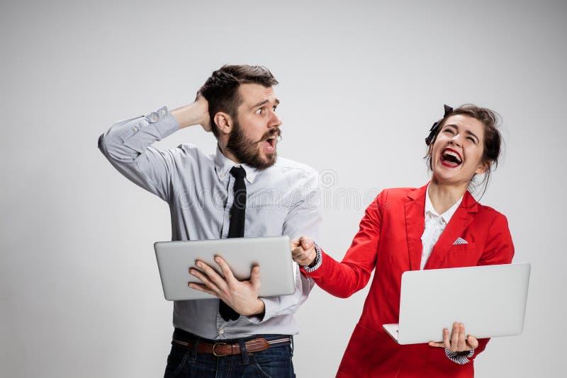 Den unga affärsmannen och affärskvinnan med bärbara datorer som meddelar på grå bakgrund arkivbild
