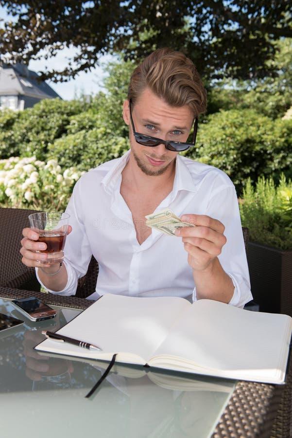 Den unga affärsmannen räknar dollar i trädgården och har royaltyfria bilder