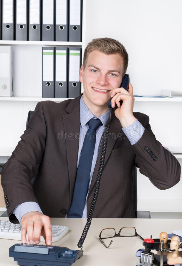 Den unga affärsmannen ringer ett nummer på telefonen arkivfoton