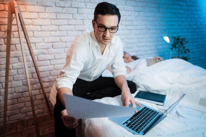Den unga affärsmannen ser arket av papper Mannen arbetar på bärbara datorn royaltyfri fotografi