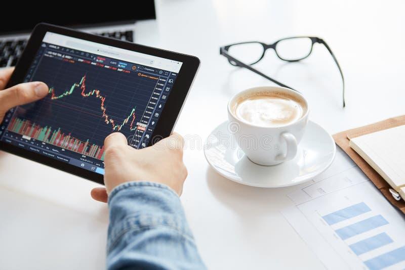 Den unga affärsmannen sitter i hem på tabellen som arbetar på minnestavlan med grafer, diagram på bildskärm Crypto valutor, affär fotografering för bildbyråer