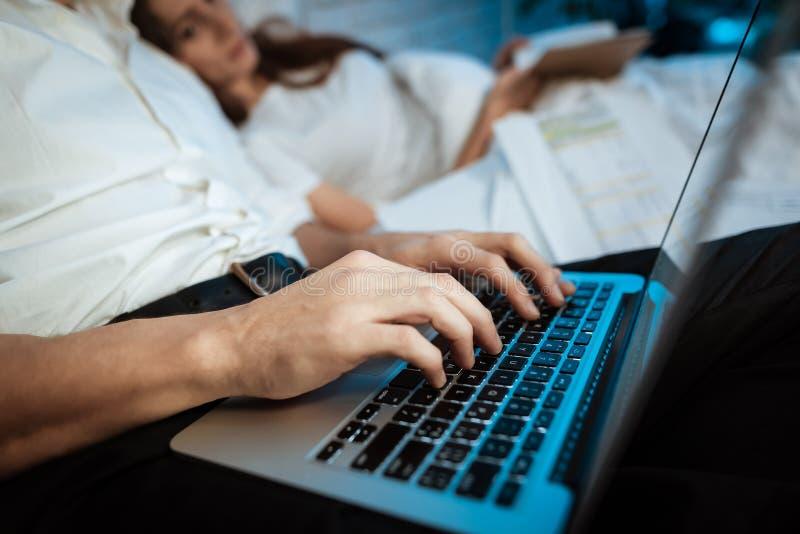 Den unga affärsmannen skriver på bärbara datorn i sovrum Kvinnan är läseboken som ligger i säng arkivfoto