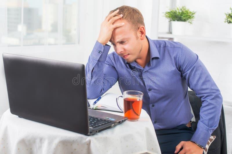 Den unga affärsmannen som arbetar i kontoret som mycket är bekymrat, löser problemet och lutade hans huvud på hans hand royaltyfri bild