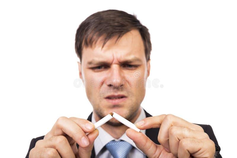 Den unga affärsmannen som bryter en cigarett, begreppet för, ger upp smok arkivfoto