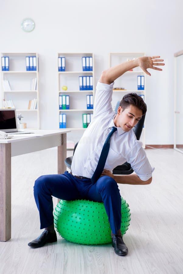 Den unga affärsmannen som gör sportar som sträcker på arbetsplatsen fotografering för bildbyråer