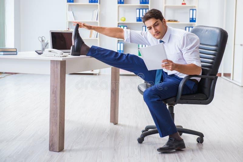 Den unga affärsmannen som gör sportar som sträcker på arbetsplatsen royaltyfri fotografi