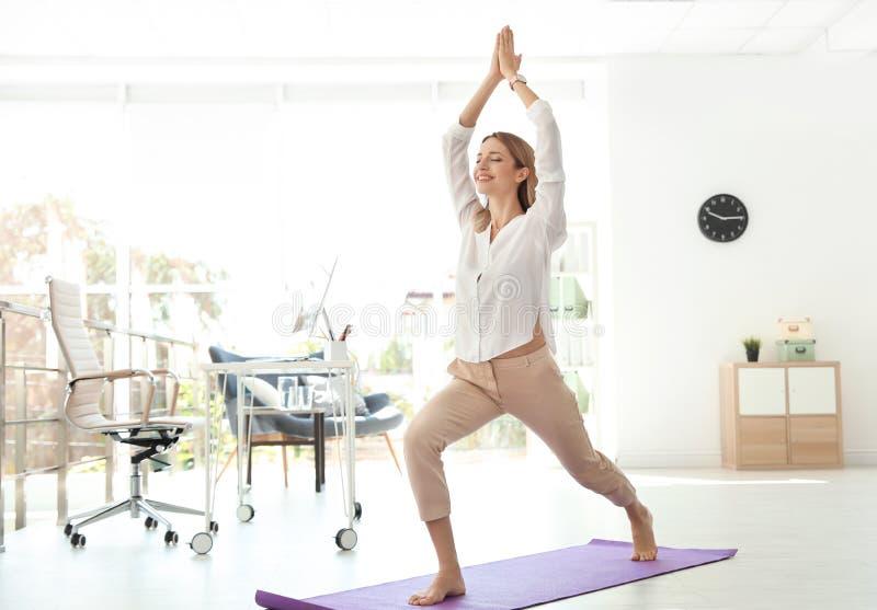 Den unga affärsmannen som gör yoga, övar i regeringsställning royaltyfria bilder