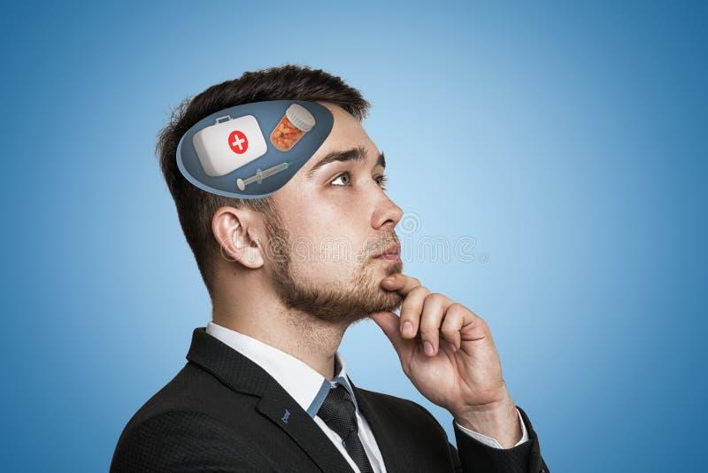 Den unga affärsmannen som tänker med första hjälpenläkarundersökningasken, piller skorrar och spolar ren i hans huvud på blå bakg arkivbilder