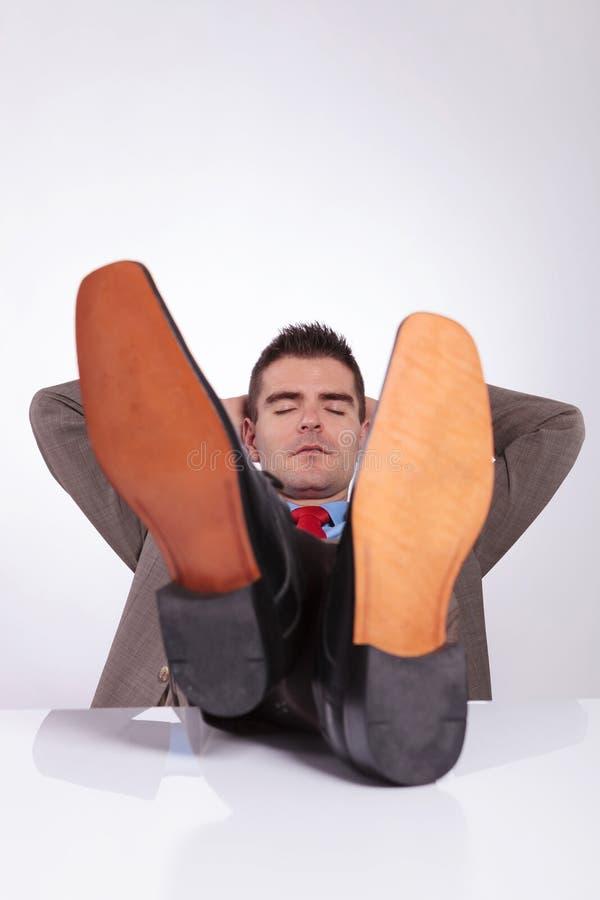 Den unga affärsmannen sover med fot på skrivbordet fotografering för bildbyråer
