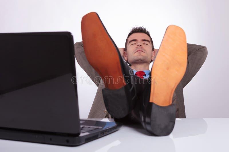 Den unga affärsmannen sover på arbete med fot på skrivbordet arkivfoton