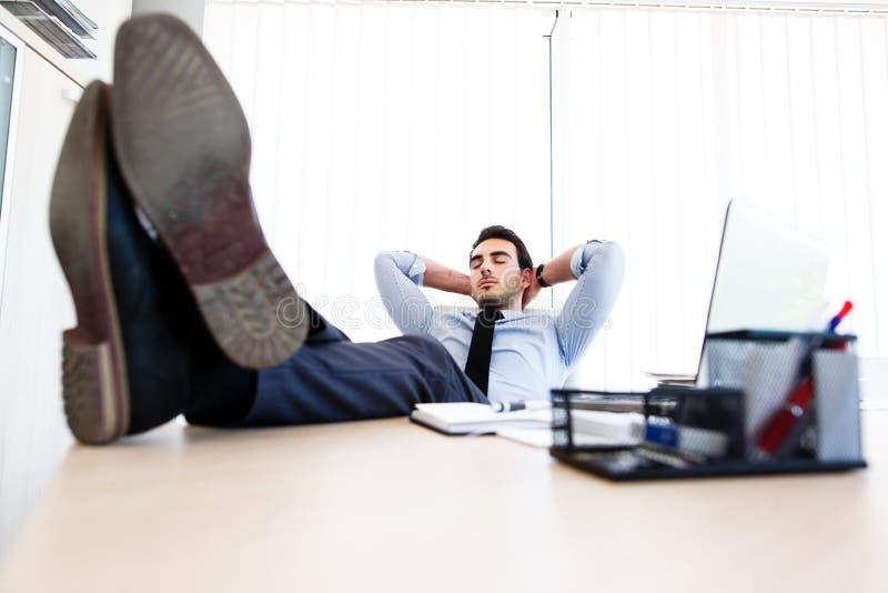 Den unga affärsmannen sover på arbetsplatsen arkivbild