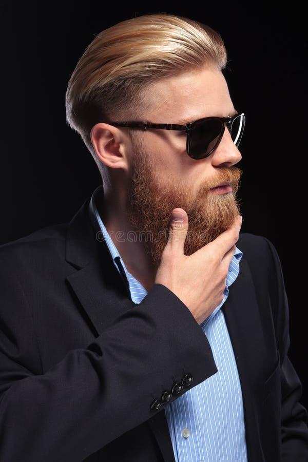 Den unga affärsmannen trycker på hans skägg fotografering för bildbyråer