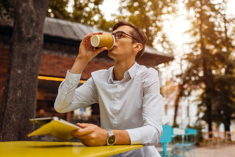 Den unga affärsmannen tycker om kaffe i utomhus- kafé genom att använda minnestavlan Stilig grabb som dricker te på stadsgatan arkivfoto
