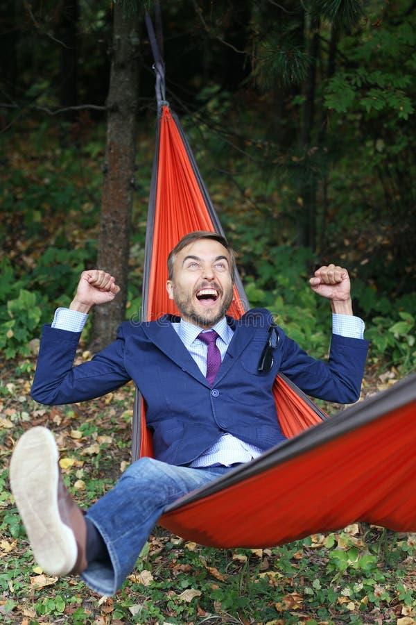 Den unga affärsmannen vilar i jätteglad hängmatta- och fellengyouself royaltyfri foto