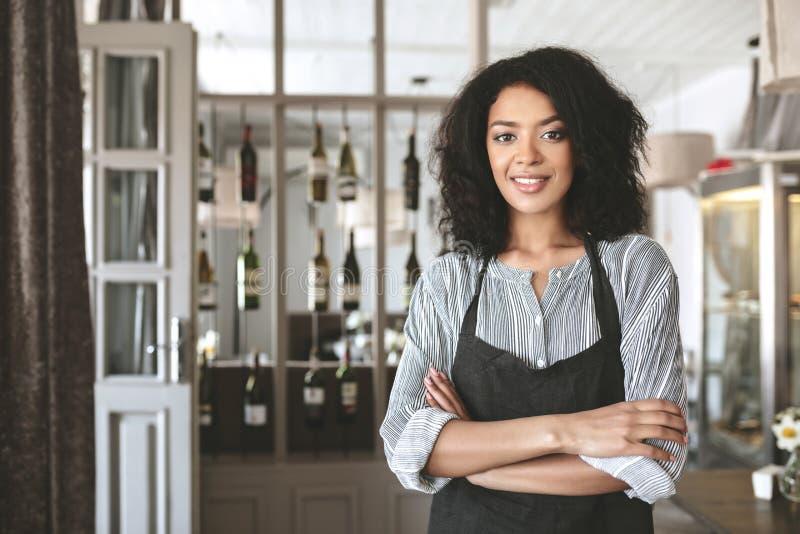 Den unga afrikansk amerikanflickan i förklädeanseende med armar vek i restaurang Trevlig flicka med mörkt anseende för lockigt hå arkivbilder