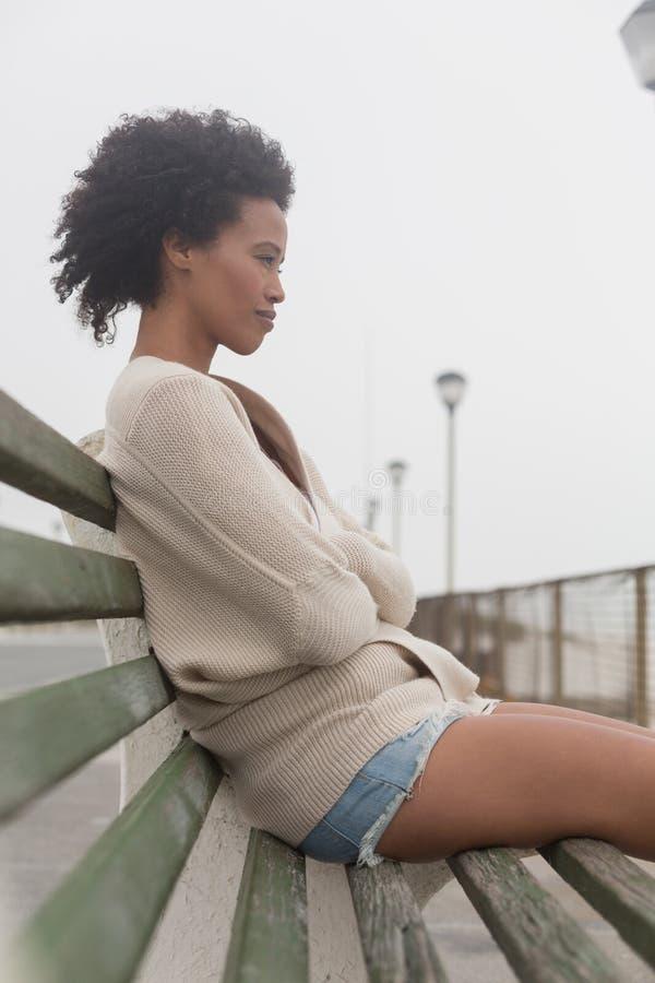 Den unga afrikansk amerikankvinnan med armar korsade att sitta på bänk på promenad fotografering för bildbyråer