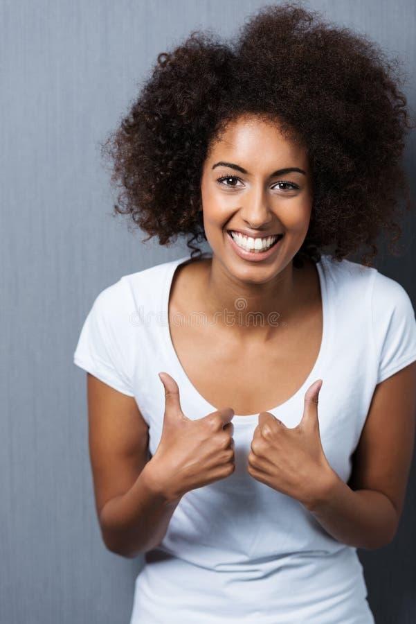 Den unga afrikansk amerikankvinnavisningen tummar upp royaltyfri fotografi
