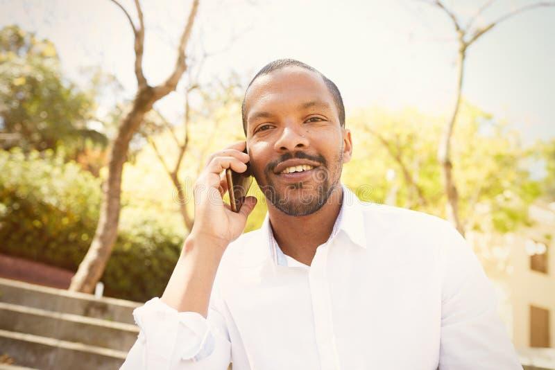 Den unga afrikansk amerikanmannen i solexponeringsglas med mobiltelefonen i stadsträdgård parkerar arkivfoto