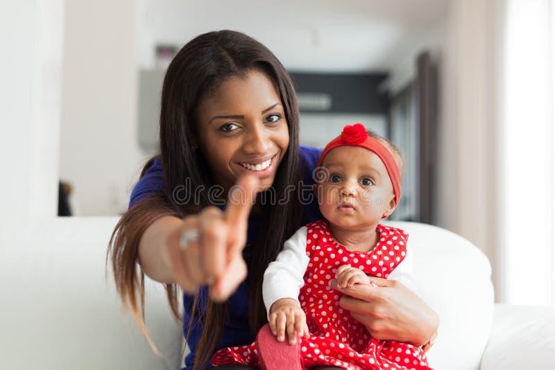 Den unga afrikansk amerikanmodern som spelar med hennes, behandla som ett barn flickan royaltyfria bilder