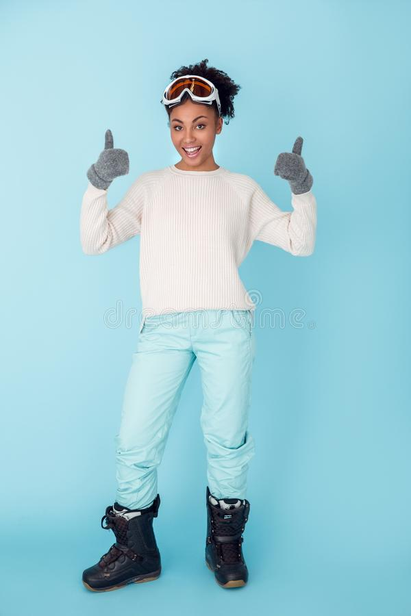 Den unga afrikanska kvinnan som isoleras på blått begrepp för sport för väggstudiovinter, tummar upp royaltyfria foton