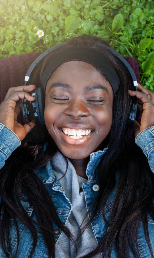 Den unga afrikanska kvinnan som lyssnar till musik som ligger i, parkerar arkivfoton