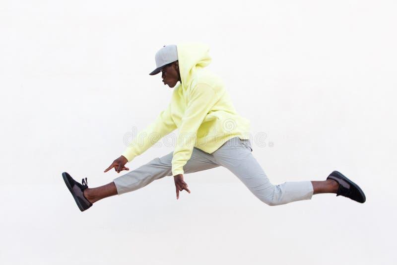 Den unga afrikanska mandansaren som gör benet, delar i mitt- luft över vit bakgrund fotografering för bildbyråer