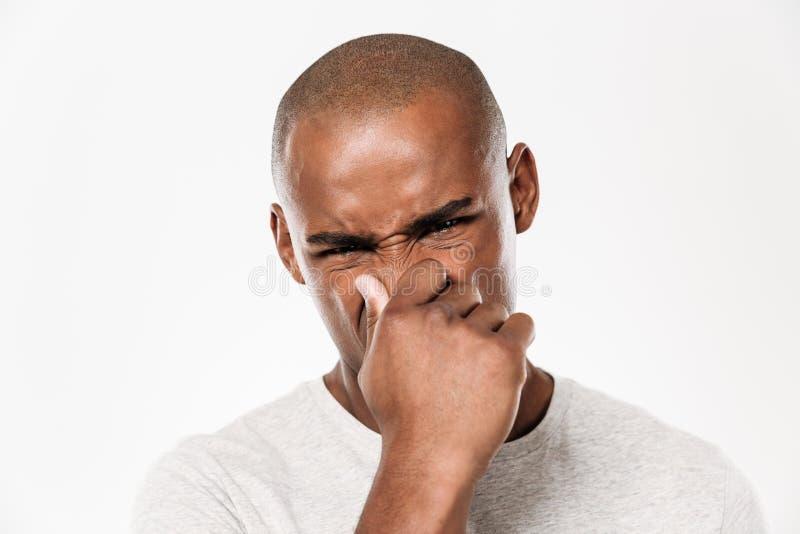 Den unga afrikanska mannen stänger en näsa från en stank royaltyfri foto