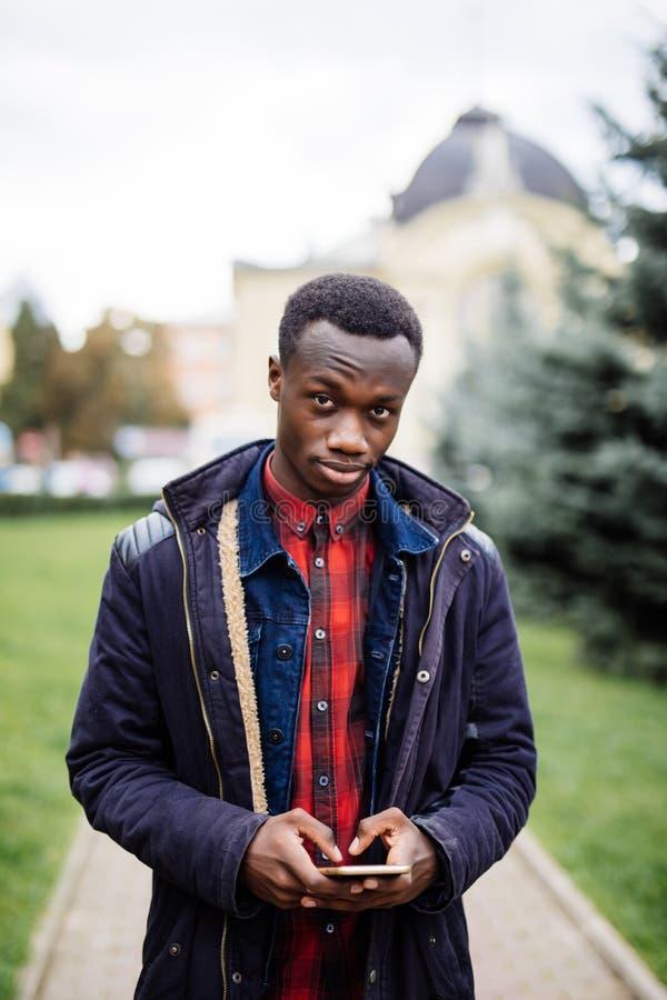 Den unga afrikanska studenten som går på, parkerar och att rymma den smarta telefonen, maskinskrivning och att prata handstilmedd royaltyfri fotografi